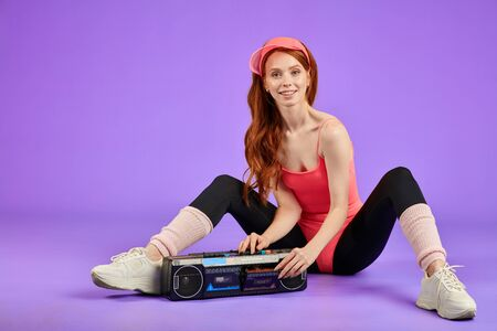 young cheerful athletic woman with red hair and flexible sporty body sits on the floor after fitness training, turning off her portable audio player, feels glad and positive, wears comfortable bodysuit and black leggins, smiles broadly, shows white teeth, looks in camera. Health and fitness concept. 스톡 콘텐츠