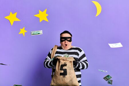excited awesome fat prisoner throwing money. isolated blue background. studio shot.