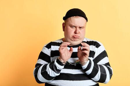 frowning sad unhappy fat man in striped clothes looking at the camera. isolated yellow background.
