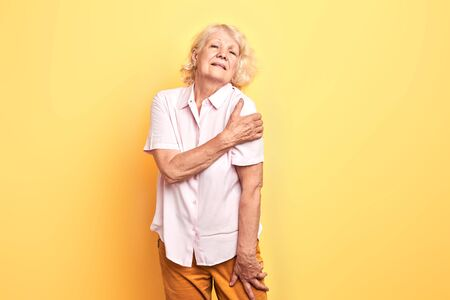 old mature attractive wman showing her shouler dislocation. isolated yellow background. studio shot.illness Zdjęcie Seryjne
