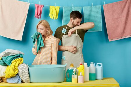 young sad couple dont like the smell of laundry. close up portrait. isolated blue background. studio shot. woman smelling cloth, towel while doing washing with husband.