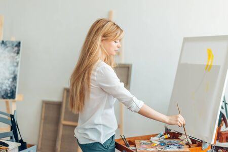 fair-haired woman painting with a brush in the art classes. close up side view photo. hobby, lifestyle, free time