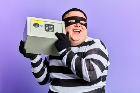 happy positive fat burglar is satisfied with a good day of crime. prisoner in striped uniform is laughing at deceived guards. isolated blue background Stock Photo