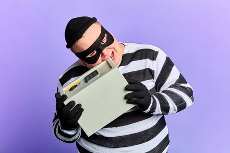 funny crazy burglar in mask trying to open safe with teeth. close up portrait. isolated blue background. studio shot Stock Photo