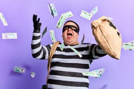 happy cheerful thief enjoying stolen money. isolated blue background studio shot. emotion and feeling Stok Fotoğraf