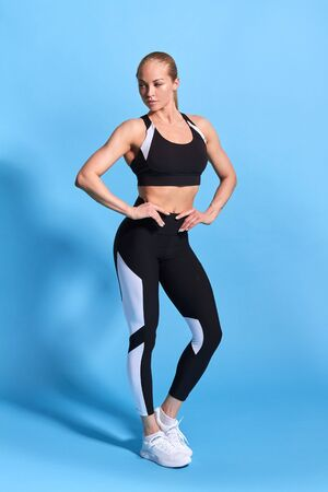 athletic young slim woman in stylish sportswear standing with hand on hip isolated on blue. full length photo. free time, sare time