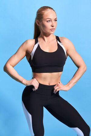 fitness slim woman has lost weight.serious confident athlete with hand on the hip looking away. studio shot. isolated blue background. lifestyle, hobby