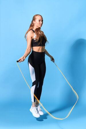 young fit woman is doing morning exercise with a rope, ful length side view photo.leisure, active life, motivation