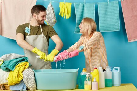 playful bearded man and blonde woman get pleasure from doing laundry. close up photo. isolated blue background. housekeeping