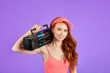 red-haired young woman with freckles looks in camera with smile, holds stereo and cassette tape player on her shoulder, wears pink sun cap and aerobics bodysuit