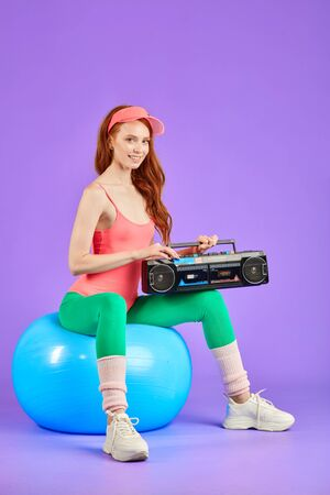 female posing for retro style photoshoot, sitting on blue fitness ball with portable cassette tape player on her knees, dressed in comfortable pink bodysuit, green leggins and white training shoes 스톡 콘텐츠