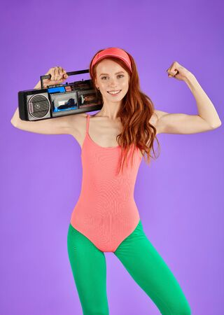 female model with long curly red hair posing for advertising catalogue of aerobics clothes, stands with portable cassette player on her shoulder and shows her biceps, body curves and sporty shape 免版税图像