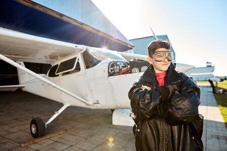 portrait of thoughtful little boy in aviator glasses, stands in large black leather pilot jacket, dreams to be a pilot when he is adult, light propeller aircraft parked behind.