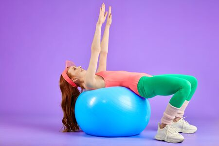 flexible female model with long red hair, laying down on fitness ball with hands up and shoulder-width apart, doing work out on abdominals and glutes, wears aerobics clothes in retro 80s style Stok Fotoğraf