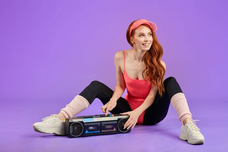 girl with nice freckles expresses positive sincere emotions, being amused friend, dressed in comfortable 80s style aerobics outwear, presses play button on portable retro audio player, sits on floor
