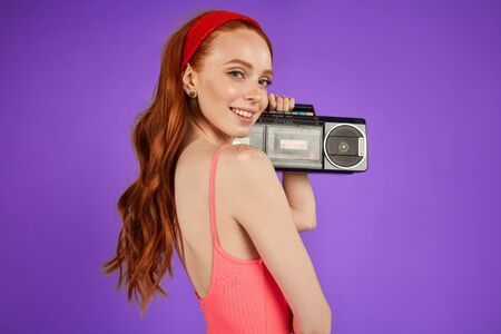 back view of motivated charming red-haired girl with green eyes and cute freckles, stands with portable audio player, looks playfully in camera with lovely smile, wears red hairband and pink bodysuit