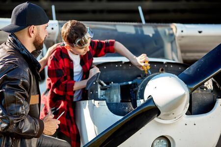 young father in black leather jacket pats his kid on the back for good job and for his progress in fixing work, giving instructions how to maintain engine block of light propeller aircraft.