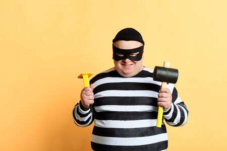 plump thief with hammer standing isolated on yellow background, close up portrait