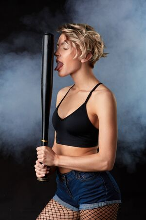 awesome pretty blond woman in stylish erotic clothes holding a bat and licking it. close up photo. isolated black background, studio shot.