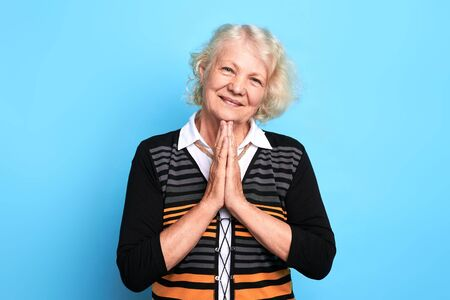 Senior happy blonde woman keeping palms together, praying the God. close up portrait. isolated blue background. strength of pray, kindness, body language, wish.