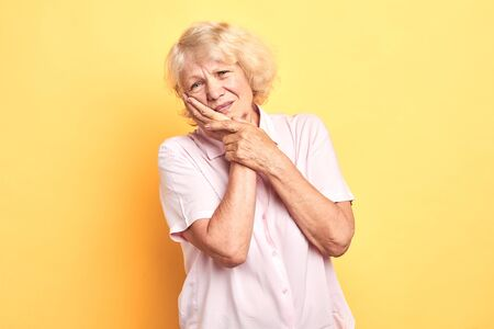blonde woman touching cheek with hand as she has problems with teeth. dental illness Dentist concept.isolated yellow background. studio shot.