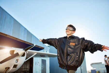 portrait of adorable boy standing with hands apart like airplane wings, dressed in dads black pilot jacket and aviator glasses, looking with smile in sky, propeller aircraft stands on background.
