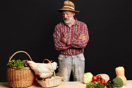 Studio shot of nice senior farmer standing with crossed hands near table with vegetables, looking at hen trying to run away from basket with eggs, smiling friendly, posing at black background.