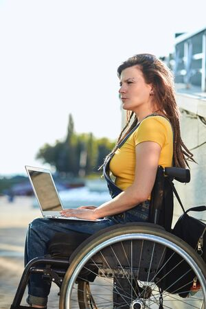 serious disabled female writer making up a story, writing a book, looking for inspiration. close up side view photo.