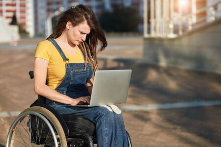 stylish disabled girl in casual clothes concentrated on working with laptop in the street, close up side view photo, copy space, blurred background.