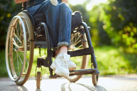 young disabled girl in overall and white trainers sitting with crossed legs on the wheelchair. close up cropped photo. Banque d'images