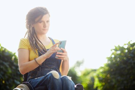 pensive woman in yellow t-shirt and overall holding her mobile phone in hands looking at the camera, Stock Photo