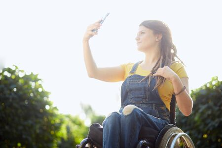 low angle view of cheerful disabled woman taking a selfie at the park