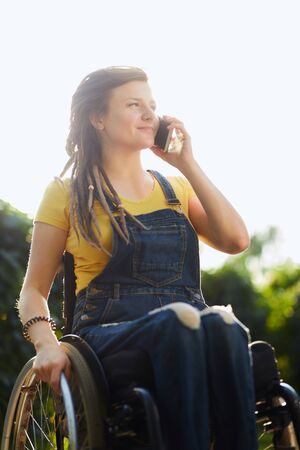 low angle view of cheerful disabled woman making a phone call at the park