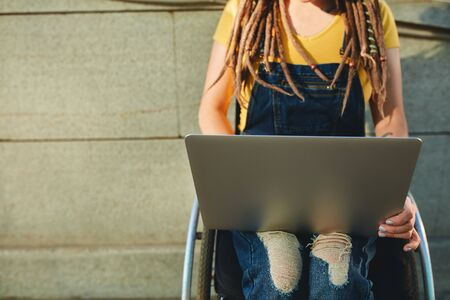 Midsection of woman using laptop while in wheelchair Stock Photo