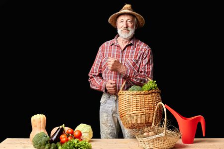 View of gray-haired mature man standing near market stall with shopping basket full of lettuce and broccoli, going to buy some more vegetables at farm market. Studio shot, isolated on black wall.
