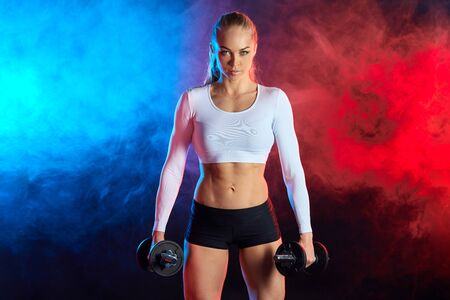 confident sexy woman in sporty clothes pumping up muscles with dumbbells isolated on black background.