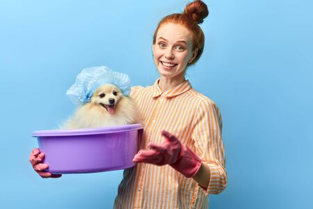 positive girl holding a basin with favourite pet and looking at the camera. isolated blue background, studio shot,interest. hobby Stockfoto