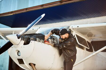 young mechanic engineer inspecting light single-engine propeller airplane constructions, fixing tube, checking engine, working hard all day long outside aircraft shed. Banco de Imagens