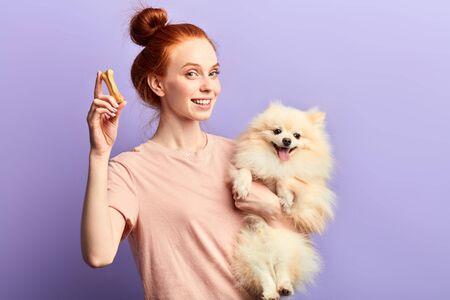 beautiful smiling red-haired girl holding adorable pet and bone and looking at the camera. close up portrait, isolated blue background, studio shot, dogs care 免版税图像