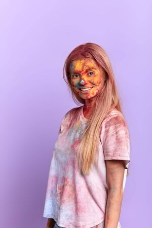 Beautiful Caucasian fair-haired girl rejoices at festive occasion of Holi, looks happily, has gentle smile, isolated over blue background. Фото со стока - 127912289