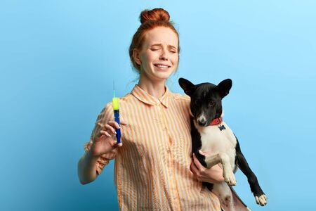 emotional ginger girl feels pity for her sick pet , owner sympathizing with poor pet. close up portrait, isolated blue background, studio shot.