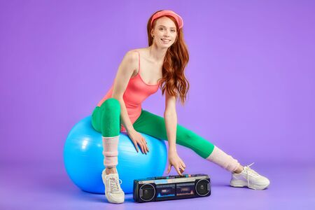 female trainer sits on blue fitness ball and press the button on her portable cassette tape player to turn on dynamic music for aerobics dance lesson, looks in camera with friendly smile Standard-Bild
