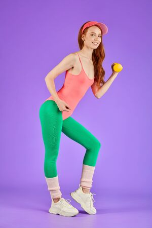 female blogger posing at personal photoshoot for her account, lifts small weights, stands with yellow dumbbell, dressed in 80s style aerobics clothes, pink bodysuit and green leggins
