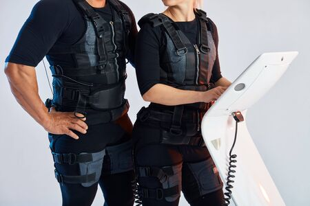 man and woman body wearing suits for electron muscle stimulation EMS.close up cropped photo.