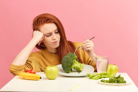 Red-haired frustrated confused disgusted displeased female model covering mouth with palms do not want to eat broccoli and veg healthy food sitting at table over pink background.