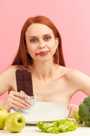 Hungry starving red-haired woman on a strict diet chooses to eat a chocolate bar instead of a healthy vegetables and fruits, feeling happiness and satisfaction from choice.