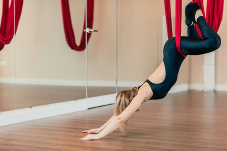 Blonde fit woman in black sportswear with naked back, working out, performing aerial yoga on ruby hammock in empty spacy studio or hall with wooden floor.