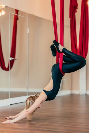 Slim yogi woman working out, performing flying aero yoga practice in red hammock in wellness centre. Advanced Yoga.