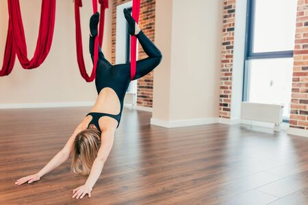 Antigarvity yoga learns also to relax and listen to thoughts and feelings. Young woman performing Aerial yoga exercise or antigravity yoga indoor. Pilates, stretch, balance, healthy lifestyle people.