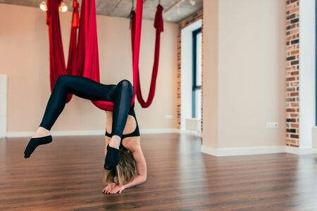 Blonde fit woman working out, performing aerial yoga on ruby hammock in class. Variation of Eka Hasta Urdhva Dhanurasana, One Hand Support Wheel Pose